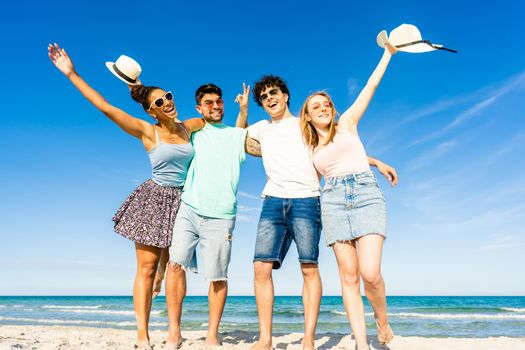 Group of multiracial young tourists posing for portrait photography in summer at tropical sea ocean resort with blue sky and crystal clear water. Happy millennial people on summer beach vacation