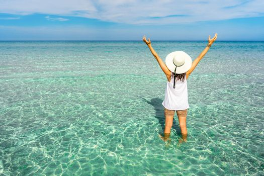 View from back of hipster unrecognizable millennial happy young woman with a large white hat in vacation resort on a crystal clear tropical sea water open arms up to the blue sky looking to horizon