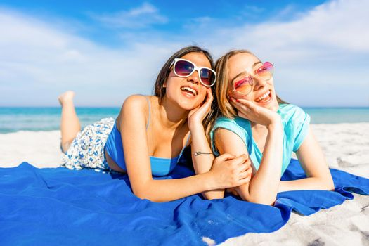 Front low view of Two happy beautiful girls lying on the tropical beach in summer vacation kissed by the sun with sunglasses smiling together. Blonde young woman with her best brunette girlfriend