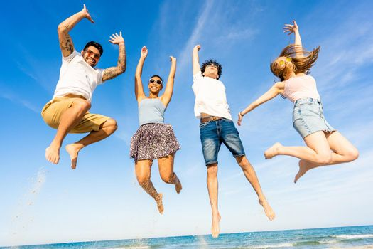 Two happy multiracial couple jumping together on the sea water with arms up to the sky smiling in vacation at tropical ocean resort. Tattoed handsome guy enjoys success celebrating with best friends