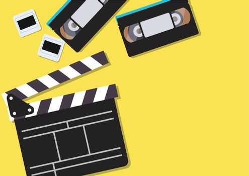 Movie clapper and video cassette tapes on yellow background