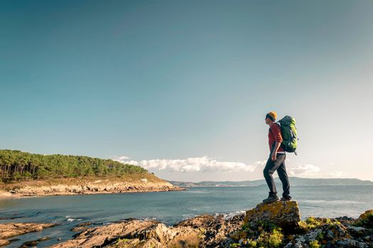 Man exploring the coastline with backpack