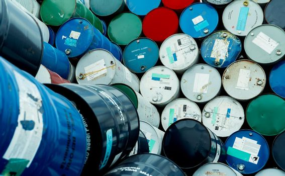Old chemical barrels. Blue, red, and green chemical drum. Steel tank. Hazard chemical barrel with flammable liquid warning label. Industrial waste. Isopropyl alcohol and aluminized orgonosol barrels.