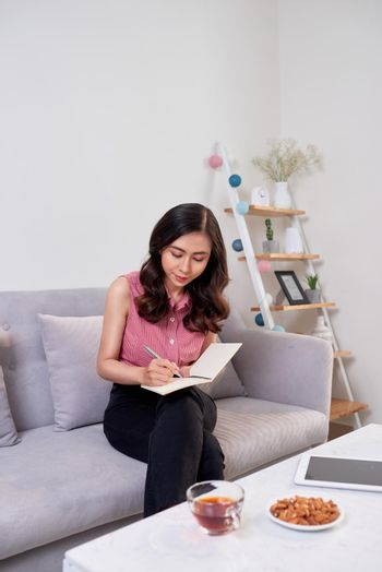 Happy pretty cute woman writing in the copybook sitting with laptop in living room