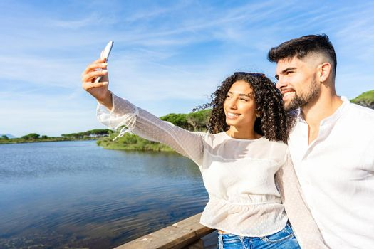 Happy couple in love making a selfie on vacation on a sea resort at sunset. Young Afro-American woman using a smartphone for a self-portrait with her boyfriend on a lake. Millennials living nature