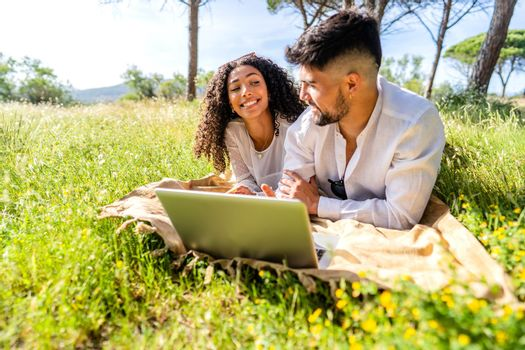 Happy couple in love using laptop in nature lying on a grass field sharing vacations on social network. Two millennial students working at pc in nature. New internet mobile connection technology