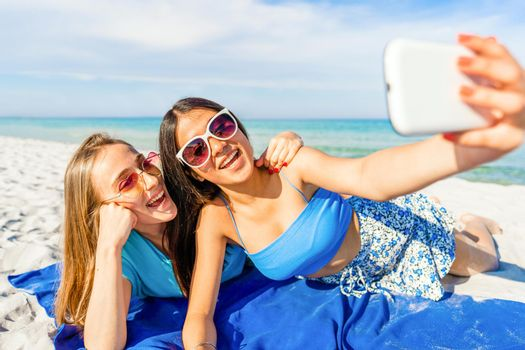 Two cute girls lying on white sand taking a self-portrait with cell wearing blue casual summer clothes and funny sunglasses on vacation at tropical beach resort with blue ocean sea on background