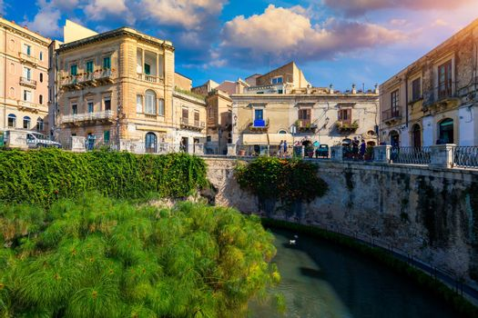 The Fountain of Arethusa and Siracusa (Syracuse) in a sunny summer day. Sicily, Italy. The Fountain of Arethusa in Ortygia, historical centre of Syracuse, Sicily, Italy.