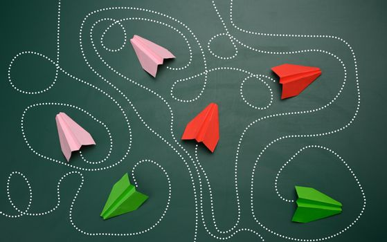 group of paper planes with long tangled paths on a green background. concept of a strong leader with extraordinary thinking