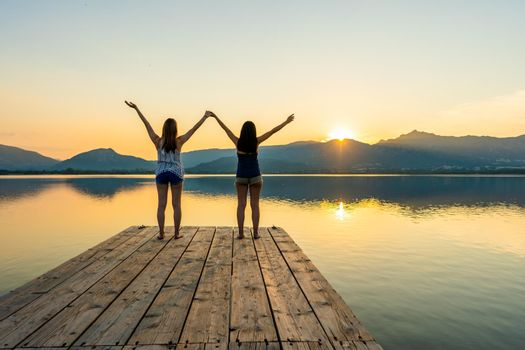 Two girls focused on spiritual meditation looking at setting sun standing on a wooden pier on flat water with light reflections. Suggestive sunset scene of pensive young women in contact with nature