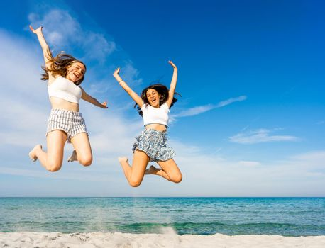 Two happy student girls jumping together looking at camera on tropical beach enjoying summer vacation in sea ocean resort. Happiness and success concept: find your talent to improve your life