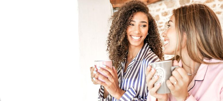 Multiracial women couple smiling looking each other holding a teacup in pajama just waken up. New normal gay families relationship and habits daily life scenes. Afro-American brunette curly woman