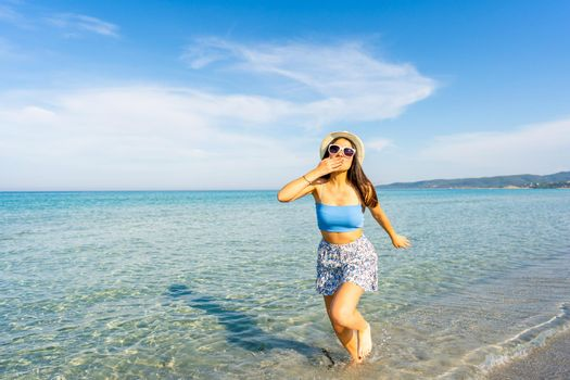 Young beautiful woman making kiss gesture with hand on mouth looking at camera walking in the seawater wearing white hat and sunglasses. Spend your time in travel for a happy better life experience