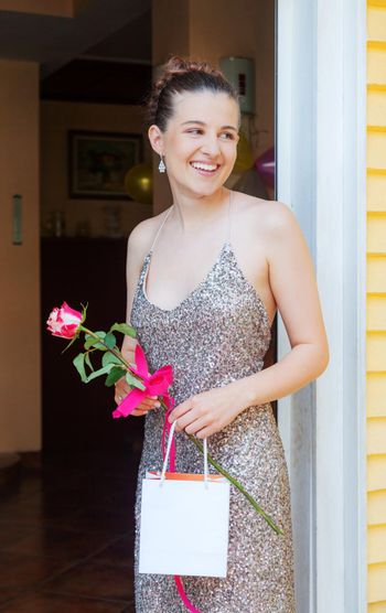 Happy Girl Graduate is Standing on the Porch Smiling Holding Empty Bag and Rose