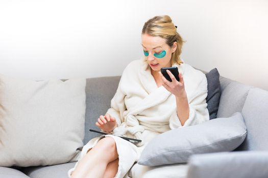 Young female entrepreneur wearing beauty face mask and cosy warm bathrobe in the morning, working remotly from her living room sofa. Remote work from home concept.