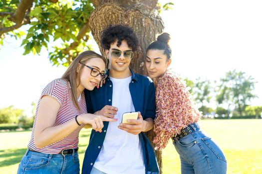 Three students having fun using smartphone at park pointing and texting on display. Two beautiful girls close to their best guy friend sharing on social network happy vacations moments