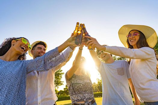 Group of young hipster friends celebrating outdoor drinking beer and toasting with bottle in front of sun setting. Happy beautiful millennials having fun with alcohol outdoor in a park at dusk