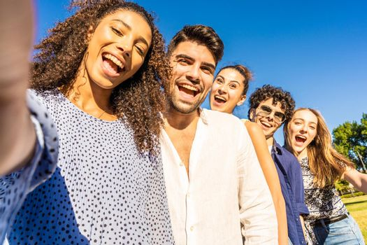Five young multiracial friends in line posing for photo portrait smiling with open mouth. Black Hispanic brunette girl taking a selfie with smartphone outdoor. POV of happy millennial carefree people