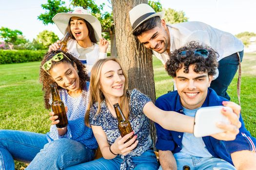 Five young multiracial friends having fun together in a picnic at city park drinking beer from bottle. Young blonde woman taking a self-portrait using smartphone to her multiracial diverse class mates