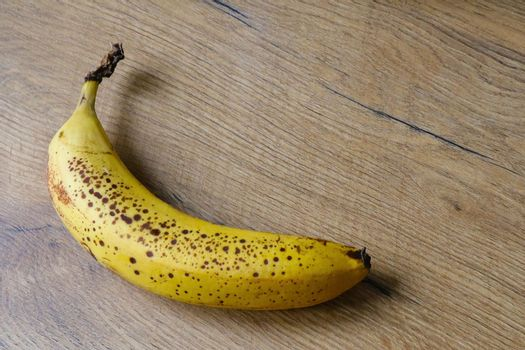 A yellow spotted banana lies on the table.