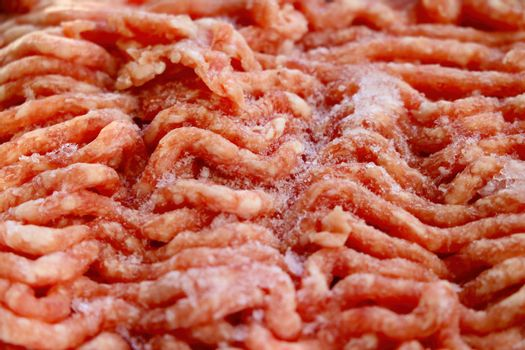 Close-up on red frozen minced meat. Background, texture of meat.