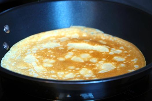 Prepare a pancake in a skillet. Light and pleasant breakfast. Homemade food.
