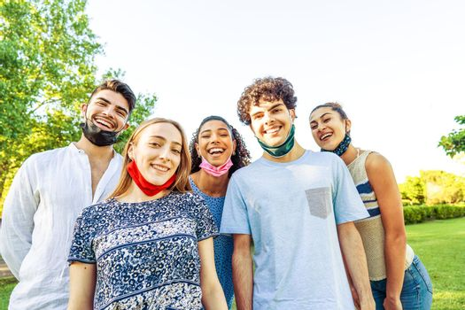 Happy carefree group of multiracial friends posing in a park for a portrait wearing lowered protective face mask so showing their beautiful smiles. Concept of happiness despite difficulties of life