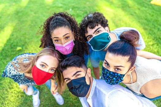Bright vivid color effect photography of multiracial group of young people looking at camera from bottom wearing colored protective face mask on a green field. New norla outdoor activity limitations