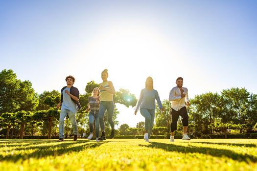Suggestive low angle view of group of young multiracial gen-z friends running on green field with setting sun at their back with light effect and long shadows on grass. Concept of people team success