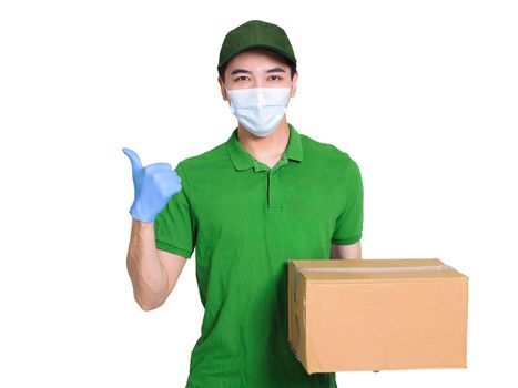 Young courier, employed wearing green clothes and hats, protective masks and gloves to protect himself, delivering packages during the covid-19 epidemic, and making a thumbs-up gesture