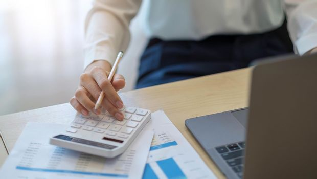 woman calculating individual income tax from financial document during note some data to sticky on window glass with calculator.