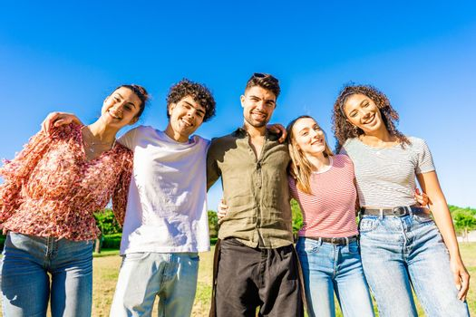 Multiracial group of college students embracing each other with arms around smiling looking at camera in a sunny day with blue sky at city park. Concept of equality and brotherhood among young people
