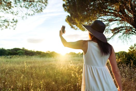 Suggestive scene from back of unrecognizable woman in white boho style dress and large dark hat taking a self portrait in front of the sun setting in the nature. Girl using cell for a self portrait