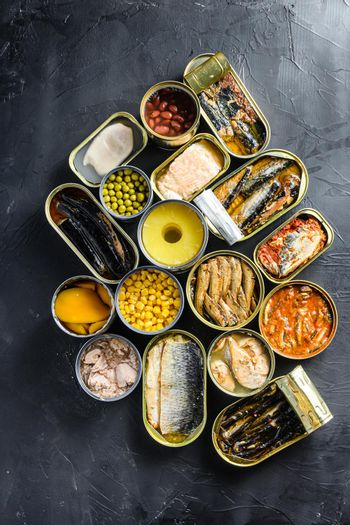 Canned conserve products in tin cans. with fresh organic ingridients Saury, mackerel, sprats, sardines, pilchard, squid, tuna pinapple, corn, peas, mango , beans, over black stone textured background topview concept
