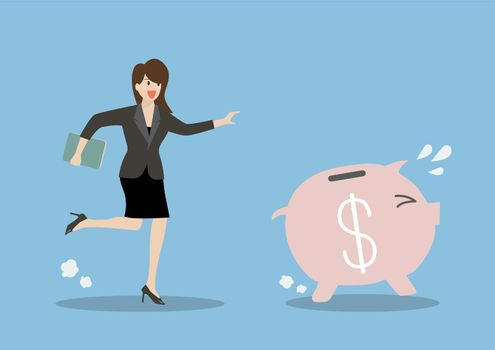 Business woman try to catch piggy bank