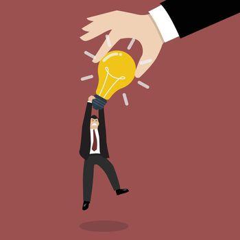 Hand stealing idea light bulb from businessman