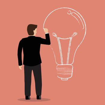 Businessman drawing lightbulb on wall