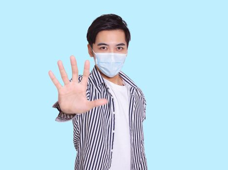 young man wears a protective medical mask to prevent COVID-19 infection and showing the stop gesture