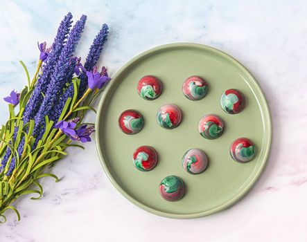 Collectible handmade tempered chocolate sweets with a glossy painted body on a round plate with blur elements. View from above. Stock photography.
