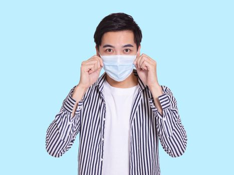 The handsome young man wears a protective medical mask to prevent COVID-19 infection and touches the mask for inspection.