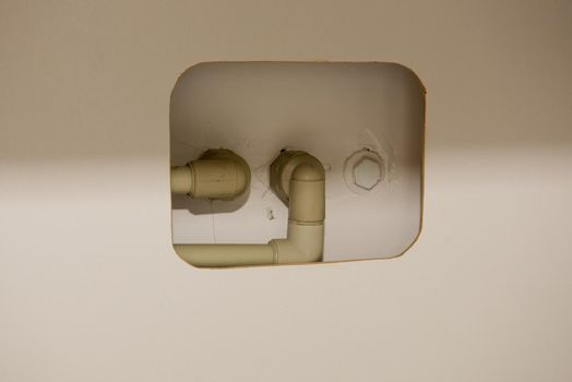 Hole in furniture for plastic water pipes in an apartment. Close-up.