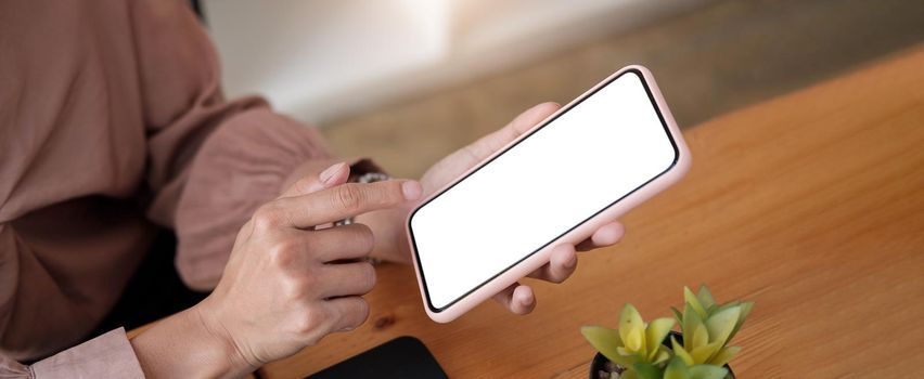 woman sitting and holding blank screen mock up mobile phone