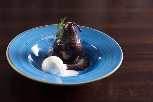 Poached pear with chocolate sauce served with a scoop of ice cre