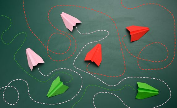 group of paper planes with long tangled paths on a green background. concept of a strong leader with extraordinary thinking, quick decision-making