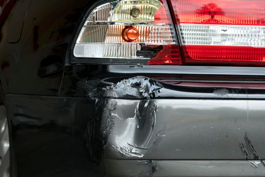 Damaged bumper and taillight on auto from collision