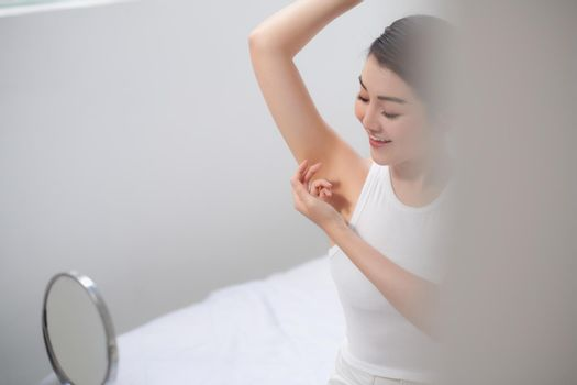 young beautiful woman raises her hands and shows her perfect clean smooth healthy skin of the armpits