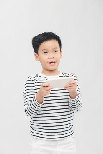 Boy enjoyed playing mobile games over white background with face expression.