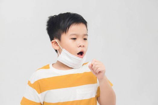 Asian boy with protective mask coughing on white background. Concept of Coronavirus epidemic