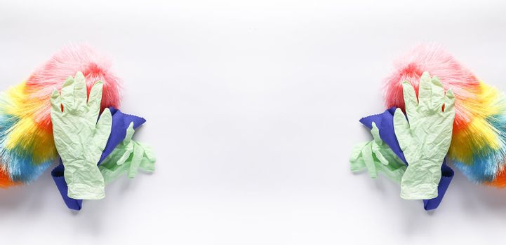 Rubber gloves, the duster and microfiber cloth on light background