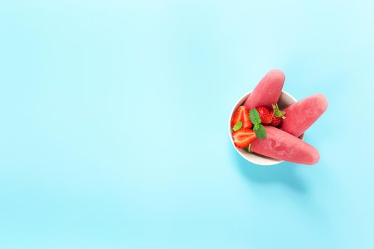 Fruity frozen sorbet ice-cream with strawberry, mint on blue background